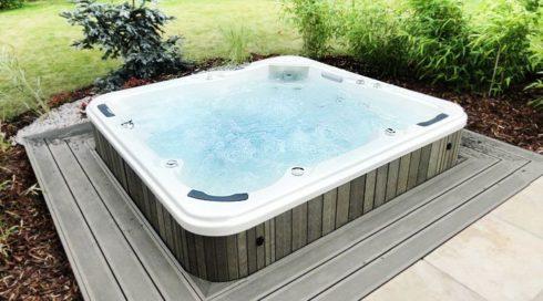 Zahradní venkovní masážní vířivka polozapuštěná na terase Canadian Spa International®